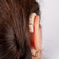 Ear of a woman with hearing aid from back