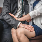 Man touching womans knee - sexual harassment in office