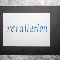 Handwritten word Retaliation. An eye for an eye concept. Italic script calligraphy.