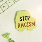 Handwriting text writing Stop Racism. Concept meaning end the antagonism directed against someone of a different race Green note paper in the shape of the car. Copy space on the green note paper.