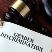 Book with chapter gender discrimination and a gavel.