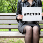 Hashtag for Mee Too movement Woman sitting on a bench at the park with a broadsheet againts sexual harassment