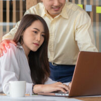 Businessman putting hand on the shoulder of female employee in office at work. She unhappy and feeling displeased with inappropriate actions his boss. Concept of sexual harassment in workplace