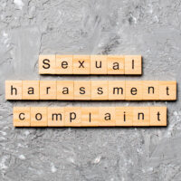Sexual harassment complaint word written on wood block. Sexual harassment complaint text on table, concept