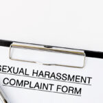 Sexual Harassment Complaint Form on attached on Clip board and pen on white background