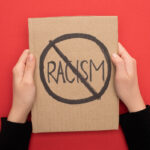 cropped view of woman holding carton placard with stop racism sign on red background