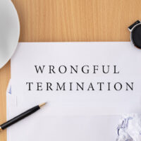 Wrongful termination document on wooden table with pen and smartwatch, termination of employment and resignation concept