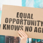 """The phrase """" Equal opportunity knows no age """" on a banner in men's hand with blurred background. Equality on workplace. Office. Job. Employment. Work. Human rights. Difference. No discrimination"""