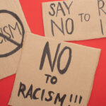 top view of carton placards with no to racism lettering on red background