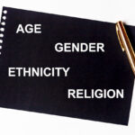 AGE GENDER ETHNICITY RELIGION words in white letters on black paper with golden pen. Equality diversity concept. Census concept
