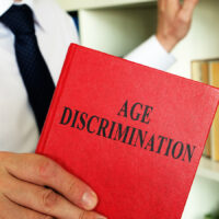 A lawyer shows an Age discrimination law book in the office.