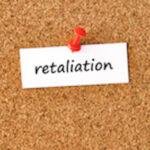 Retaliation. Word written on a piece of paper, cork board background.