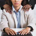 Sexual harassment problem. Close up of boss touching his beautiful female assistant at workplace, panorama