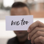 man showing a note with the text me too