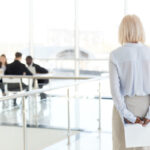 Rear view at stressed nervous senior businesswoman waiting for i