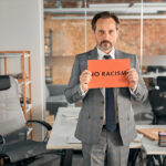 Serious man standing in office and holding no racism placard