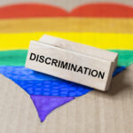 Discrimination word on wooden block on lgbtq flag in heart