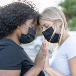 African and white northern women together and wearing protective face masks - Black lives matter concept - Girlfriends, love and no racism