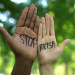 Interracial people hands with stop racism phrase, fight against discrimination
