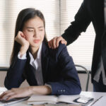 Asian women sexual harassment at working in the office Manager putting his hand on the shoulder of his