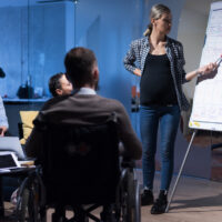 Handicapped young man with his colleagues working in office. Disabled businessman in the wheelchair and his colleagues listetning presentation of their pregnant female colleague.