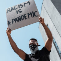 low angle view of african american man with scarf on face holding placard with racism is a pandemic lettering near building