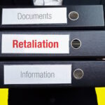 Retaliation. Man carries stack of folders. File folders with text label. Background yellow.