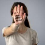 Stop sexual assault sign on womans hand, discrimination prevention, assault