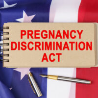 Against the background of the flag of the USA lies a notebook with the inscription - PREGNANCY DISCRIMINATION ACT