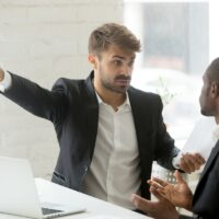 Rude white partner telling black businessman get out his office