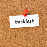 Backlash. Word written on a piece of paper, cork board background.