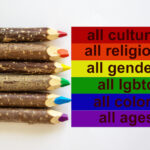 LGBT colors corrugated cardboard flag. Pencils lie on top Bright social colors lgbt. Diversity ethnicity gender age sexual orientation religion disability words. Copy space. Equality and diversity concept.
