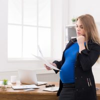 Pregnant business woman talking on phone at office